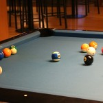 Image of a pool table with a game in progress